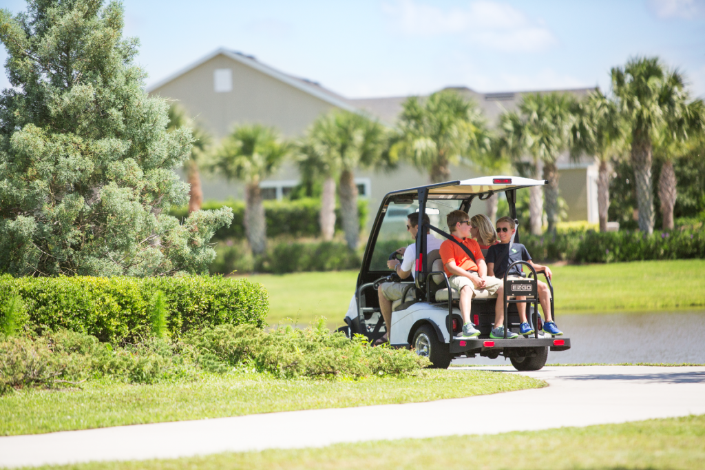 2 adults and 2 teenagers riding on a golf cart on Viera Multi-Use Trails